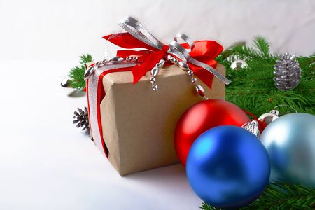 Christmas background with silver beads decorated gift box. Christmas background with red and blue ornaments. Stock Photo