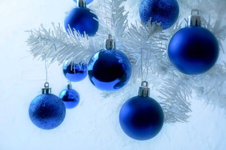 Christmas background with white fir branch and blue ornament. Christmas greeting background. Stock Photo