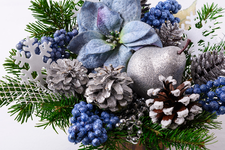 Christmas flower arrangement with blue silk poinsettias. Christmas background with decorated pine cones.