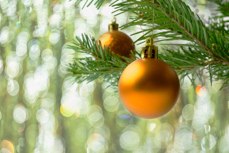 Christmas tree branch with golden balls. Christmas greeting background with fir branch and golden  ornaments. Christmas decoration with bauble hanging. Copy space. Stock Photo