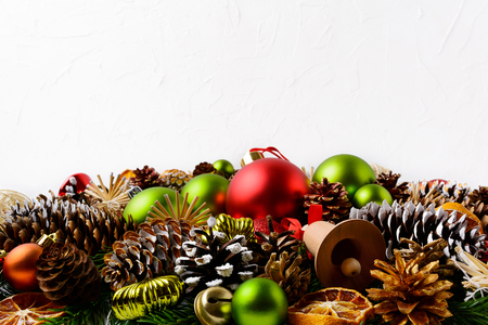 Christmas greeting background with hand decorated pine cones. Christmas decoration with green ornaments and dried orange slices. Copy space.