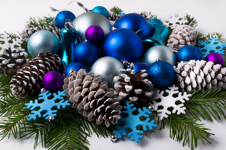 Christmas decoration with purple and blue color shades ornaments. Christmas greeting background with blue balls, fir branches and felt snowflakes.