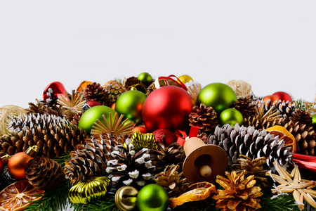 Traditional Christmas ornaments, fir branches and pine cones. Christmas decoration with baubles and dried orange slices. Christmas greeting background. Copy space. Stock Photo