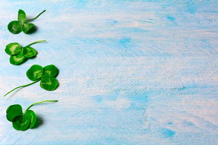 patrics: St. Patricks day greeting card with shamrock. Border of Clovers leaves on blue wooden background. Copy space.