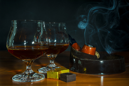 Scotch drink and tobacco pipe with smoke on black background. Two old fashioned whiskey glass  and chocolate piece. Unhealthy still life or bad habits concept. Clear brandy or bourbon snifter. Stock Photo