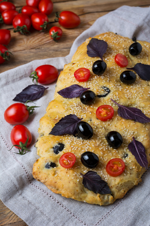 Ciabatta with olive, sesame, basil leaves and cherry tomato. Homemade traditional Italian bread focaccia on the linen napkin. Vertical.