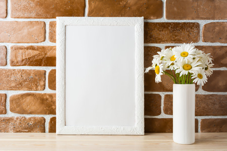 White frame mockup with daisy bouquet in styled vase near exposed brick wall. Empty frame mock up for presentation design.  Template framing for modern art.