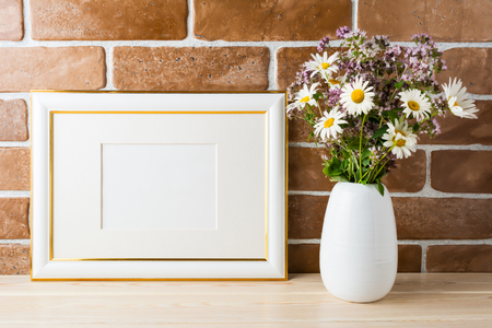 Gold decorated landscape frame mockup with wildflowers bouquet in styled vase near exposed brick wall. Empty frame mock up for presentation design.  Template framing for modern art.  Banque d'images