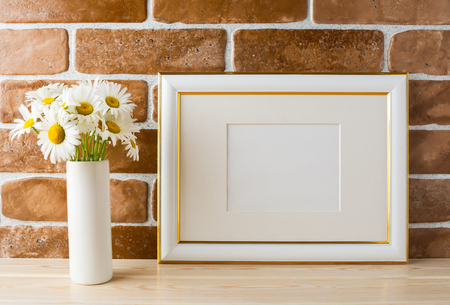 Gold decorated landscape frame mockup with daisy bouquet in styled vase near exposed brick wall. Empty frame mock up for presentation design.  Template framing for modern art.