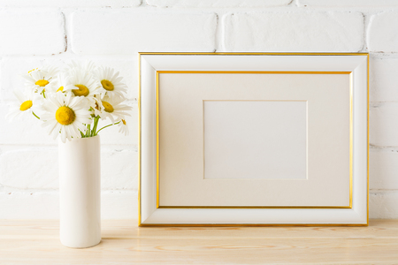 Gold decorated landscape frame mockup with wild daisy flower in styled vase near painted brick wall. Empty frame mock up for presentation design.  Template framing for modern art.