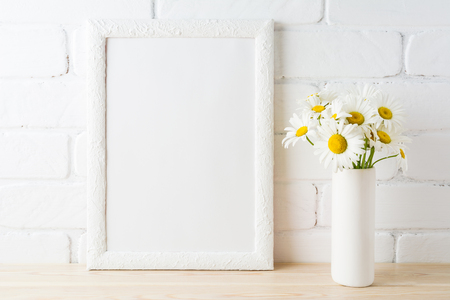 White frame mockup with daisy flower in styled vase near painted brick wall. Empty frame mock up for presentation design.  Template framing for modern art. Banque d'images