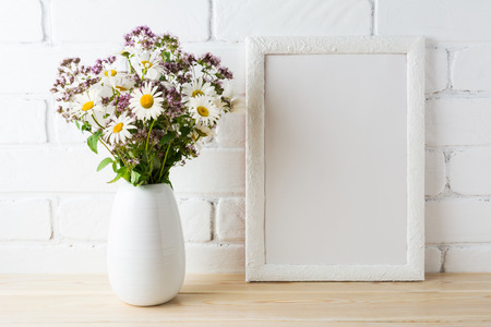 White frame mockup with blooming wildflower bouquet in in styled vase near painted brick wall. Empty frame mock up for presentation design.  Template framing for modern art.