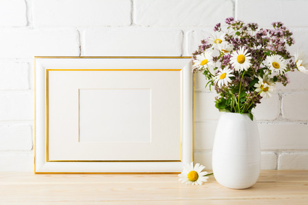 Gold decorated landscape frame mockup with blooming wildflower bouquet in styled vase near painted brick wall. Empty frame mock up for presentation design.  Template framing for modern art.