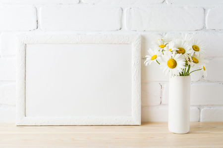 White landscape frame mockup with daisy flower in styled vase near painted brick wall. Empty frame mock up for presentation design.  Template framing for modern art.
