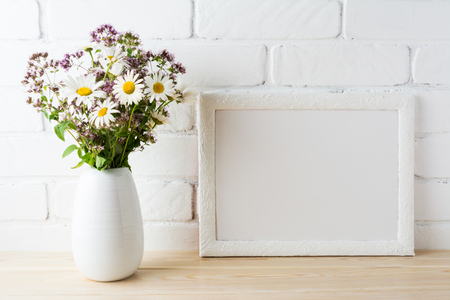 White landscape frame mockup with blooming wildflower s bouquet in styled vase near painted brick wall. Empty frame mock up for presentation design.  Template framing for modern art.