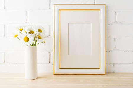 Gold decorated frame mockup with wild daisy flower in styled vase near painted brick wall. Empty frame mock up for presentation design.  Template framing for modern art.  Banque d'images