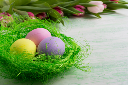 Three Easter eggs in green nest. Happy Easter greeting card or invitation. Copy space. Stock Photo
