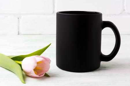 stock photo   tulip: Black coffee mug mockup with tender pink tulip flower. Empty mug mock up for brand promotion.