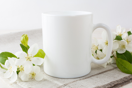 White coffee mug mockup with blossoming apple tree branch.  Empty mug mock up for design promotion.