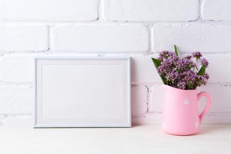White metal landscape frame mockup with purple field flowers in polka dot pink rustic pitcher vase. Empty frame mock up for presentation artwork. Template framing for modern art.