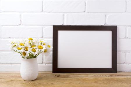 Black brown  landscape frame mockup with white field chamomile bouquet in handmade rustic vase. Empty frame mock up for presentation design. Template framing for modern art.