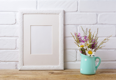 White frame mockup with white chamomile and purple field flowers in mint green pitcher vase. Empty frame mock up for presentation artwork. Template framing for modern art. Banque d'images