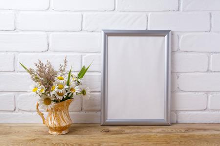 Silver frame mockup with white field chamomile and grass in golden pitcher vase. Empty frame mock up for presentation artwork. Template framing for modern art.