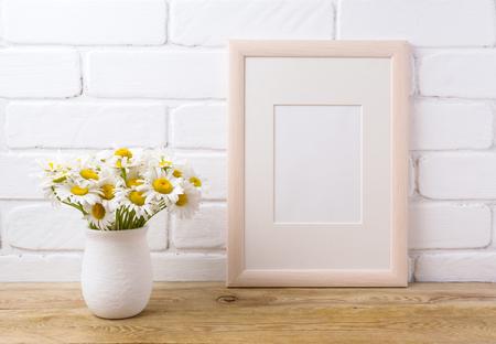 Wooden frame mockup with white field chamomile bouquet in handmade rustic vase. Empty frame mock up for presentation design. Template framing for modern art.