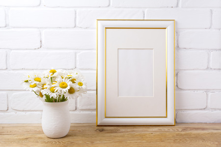 Gold decorated frame mockup with white field chamomile bouquet in handmade rustic vase. Empty frame mock up for presentation artwork. Template framing for modern art. Banque d'images