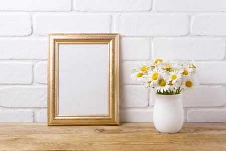 Golden frame mockup with white field chamomile bouquet in handmade rustic vase. Empty frame mock up for presentation artwork. Template framing for modern art.