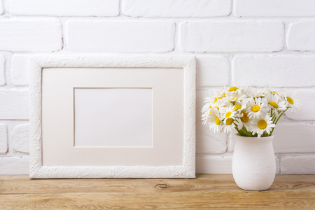 White landscape picture frame with mat  mockup with white field chamomile bouquet in handmade rustic vase. Empty frame mock up for presentation artwork. Template framing for modern art.
