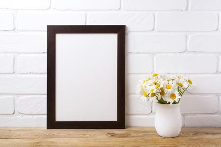 Black brown  frame mockup with white field chamomile bouquet in handmade rustic vase. Empty frame mock up for presentation design. Template framing for modern art. Banque d'images