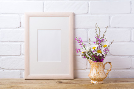painted wood: Wooden frame mockup with white chamomile and purple field flowers in golden pitcher vase. Empty frame mock up for presentation design. Template framing for modern art.
