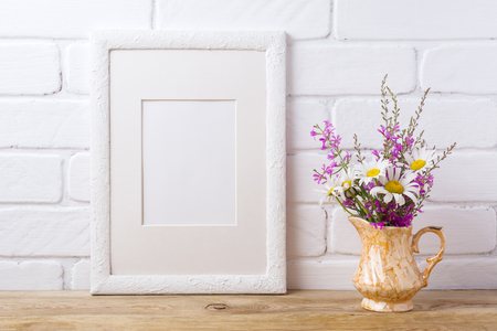 White picture frame with mat  mockup with white chamomile and purple field flowers in golden pitcher vase. Empty frame mock up for presentation artwork. Template framing for modern art.