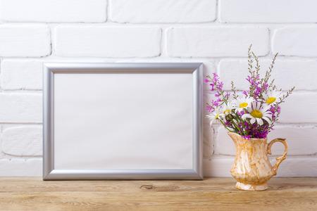Silver landscape frame mockup with white chamomile and purple field flowers in golden pitcher vase. Empty frame mock up for presentation artwork. Template framing for modern art.