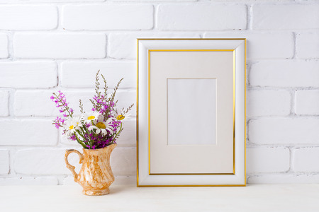 Gold decorated frame mockup with white chamomile and purple field flowers in golden pitcher vase. Empty frame mock up for presentation artwork. Template framing for modern art.