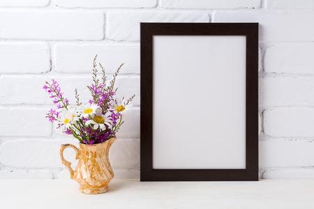 Black brown  frame mockup with white chamomile and purple field flowers in golden pitcher vase. Empty frame mock up for presentation design. Template framing for modern art.