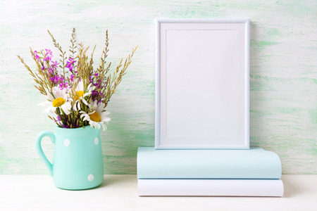 White frame mockup with white chamomile and purple field flowers in mint green pitcher vase and books. Empty frame mock up for presentation artwork. Template framing for modern art.