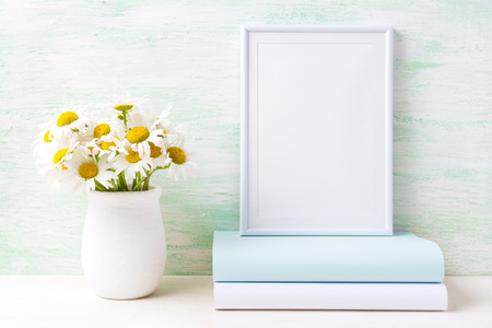White frame mockup with white field chamomile bouquet in handmade rustic vase and books. Empty frame mock up for presentation artwork. Template framing for modern art.