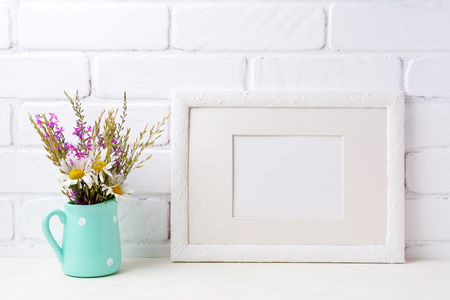 White landscape picture frame with mat  mockup with white chamomile and purple field flowers in mint green pitcher vase. Empty frame mock up for presentation artwork. Template framing for modern art.