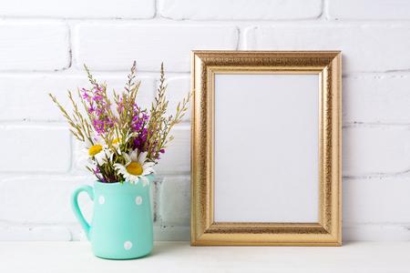 Golden frame mockup with white chamomile and purple field flowers in mint green pitcher vase. Empty frame mock up for presentation artwork. Template framing for modern art.