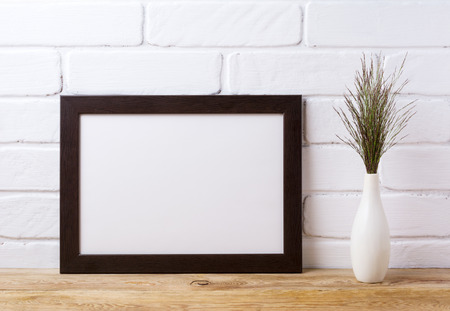 Black brown  landscape frame mockup with dark meadow grass in elegant vase near painted brick wall. Empty frame mock up for presentation design. Template framing for modern art.