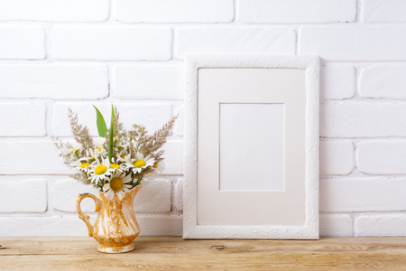 White picture frame with mat  mockup with white field chamomile and grass in golden pitcher vase. Empty frame mock up for presentation artwork. Template framing for modern art.