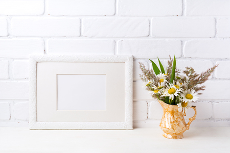White landscape picture frame with mat  mockup with white field chamomile and grass in golden pitcher vase. Empty frame mock up for presentation artwork. Template framing for modern art.