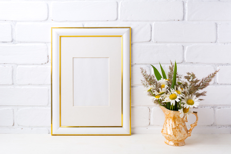 Gold decorated frame mockup with white field chamomile and grass in golden pitcher vase. Empty frame mock up for presentation artwork. Template framing for modern art.