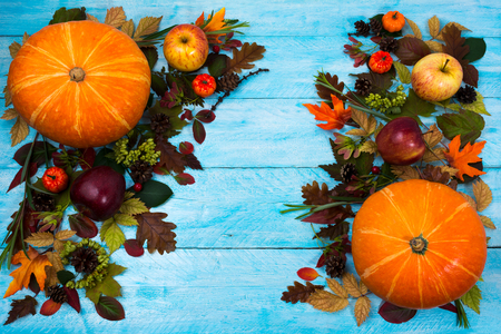 Thanksgiving  greeting with pumpkin, apples and autumn leaves on blue wooden table. Fall background with seasonal vegetables and fruits, copy space