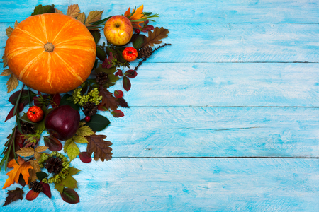 Happy Thanksgiving  greeting with pumpkin, apples and autumn leaves on the left side of blue wooden table. Fall background with seasonal vegetables and fruits, copy space Stock Photo