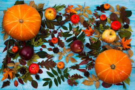 cuerno de la abundancia: Thanksgiving  greeting with pumpkin, apples and autumn leaves on blue wooden table. Fall background with vegetables, cones and fruits