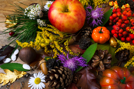 Thanksgiving  greeting with pumpkin, apples, autumn leaves, berries and flowers on wooden table. Fall background with seasonal vegetables and fruits