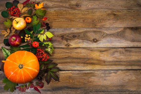 Happy Thanksgiving background with squash, apples and autumn leaves on the right side of rustic wooden table. Fall decor with seasonal vegetables and fruits, copy space